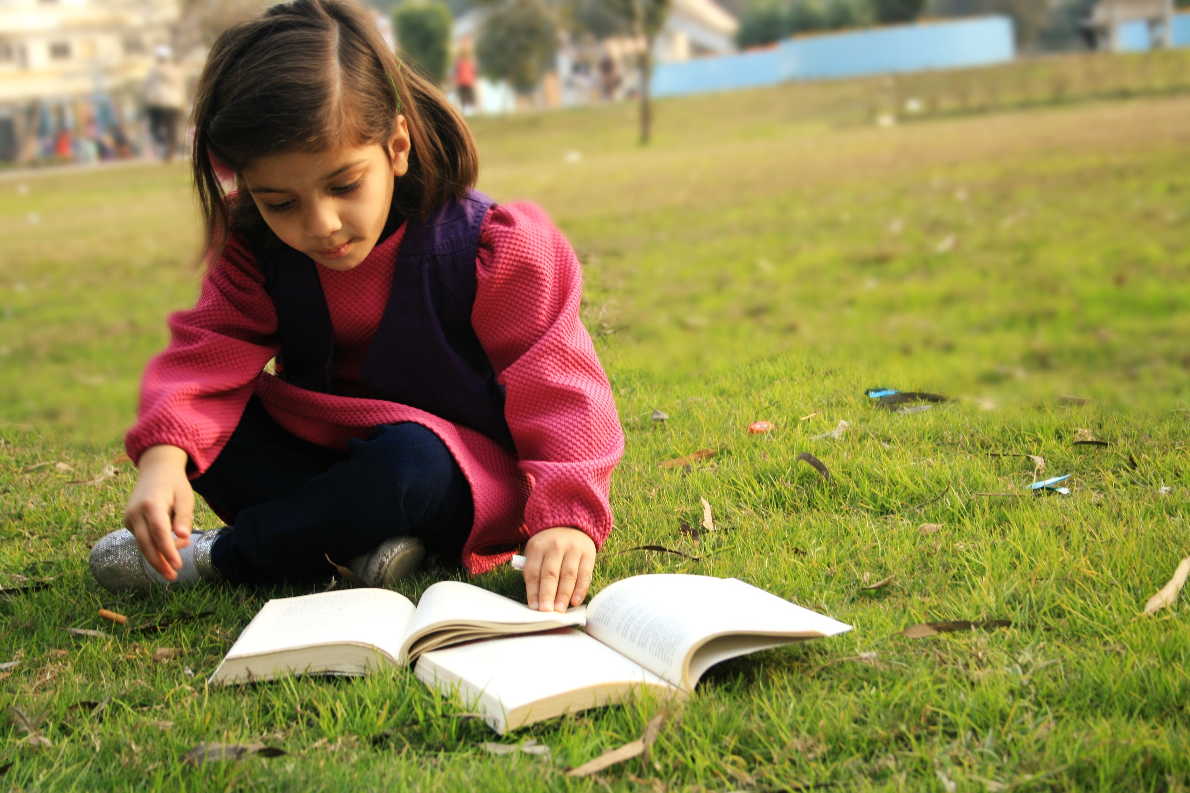 Young girl reading book outside