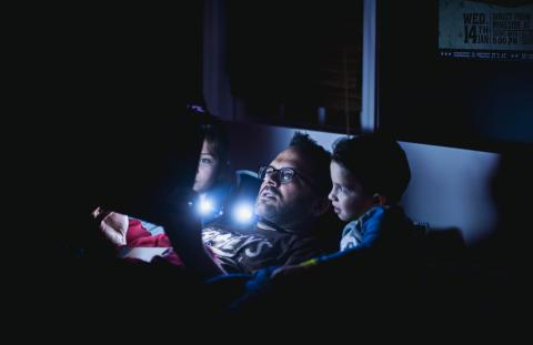 father reading to children in bed