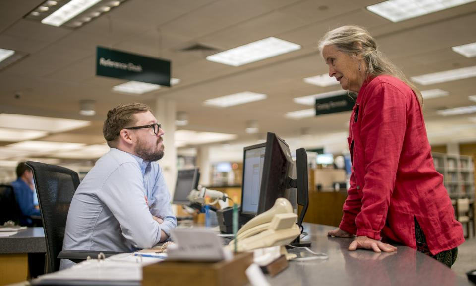 man and woman at reference desk