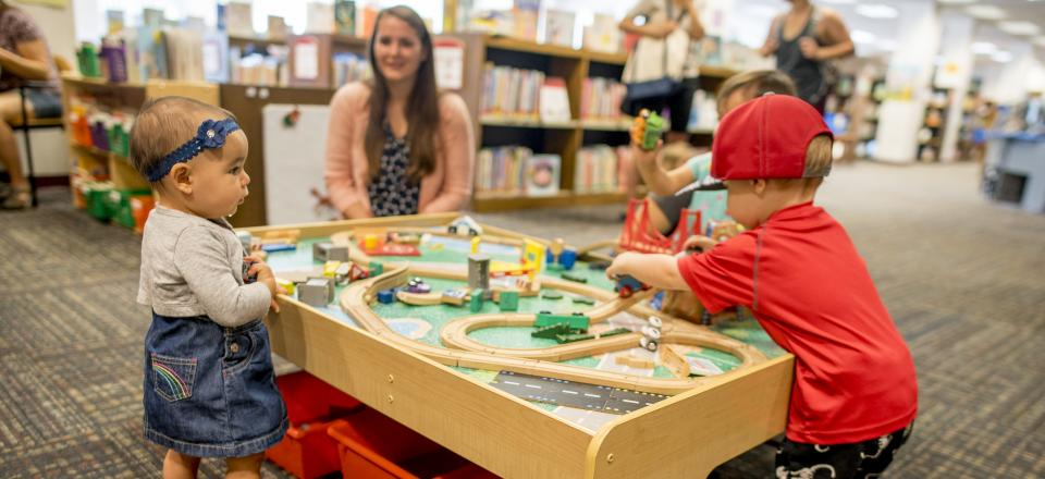 Children playing with wooden train set on a table.
